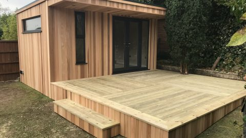Cedar clad games room, built in Bristol. With large decking that wraps around a large tree