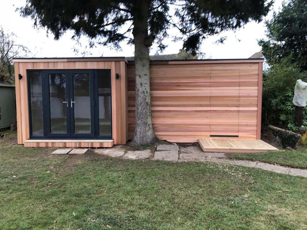 Bespoke 'L' shaped cedar clad garden room, with intergrated shed and a hidden cedar door