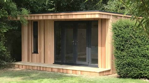 Cedar clad garden room with a canopy, sitting in between bushes in well established garden