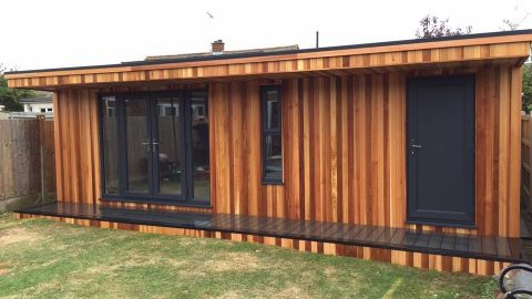Cedar clad garden games room, sits snug at the bottom of a garden.
