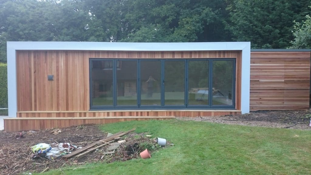 A garden room / pool room with outdoor changing room and gym/office