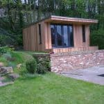 Garden room set behind a brick retaining wall