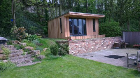 Garden cabin set behind a brick retaining wall