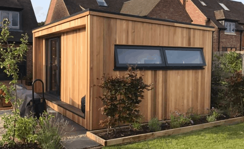 Garden Rooms Prices - Guide to Costs Cedar cladded garden room used as a home office with aluminium windows and doors, composite decking