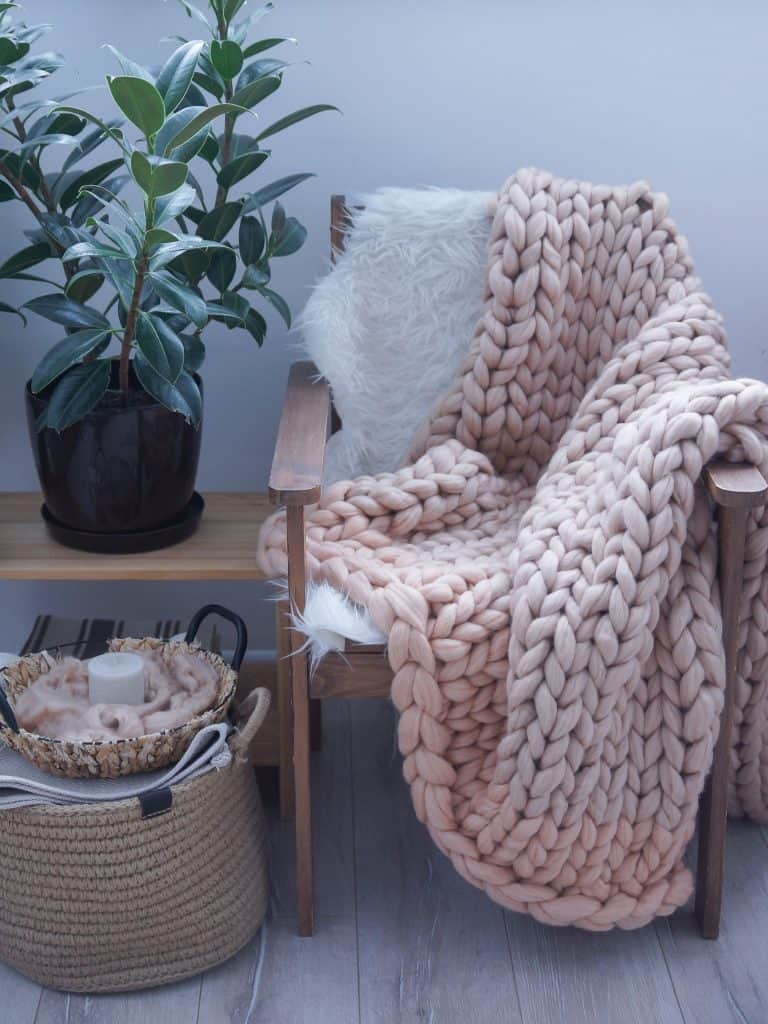 5 Ways to Practice Hygge in Your Insulated Summer House - a chunky knit throw and a candle