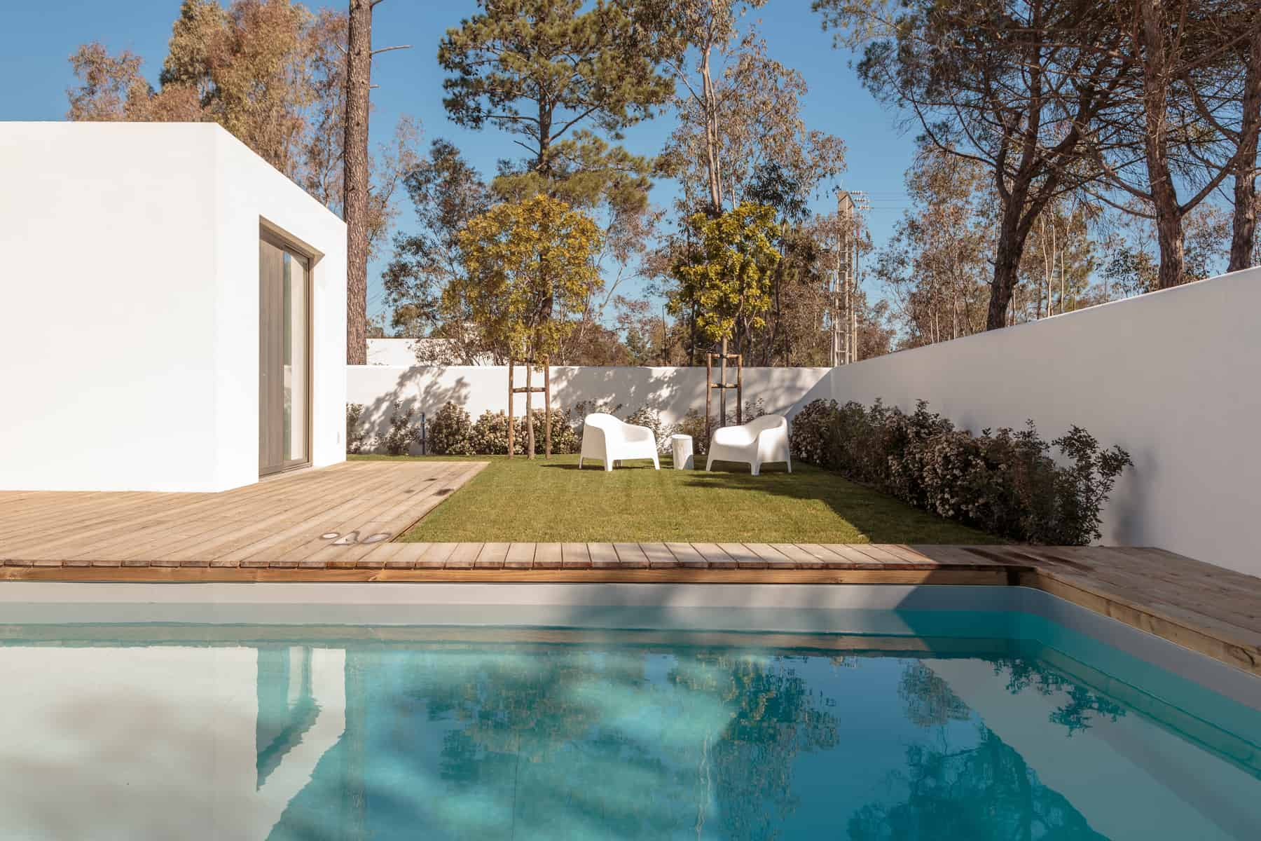 Modern house with garden swimming pool and wooden deck and garden room pool house